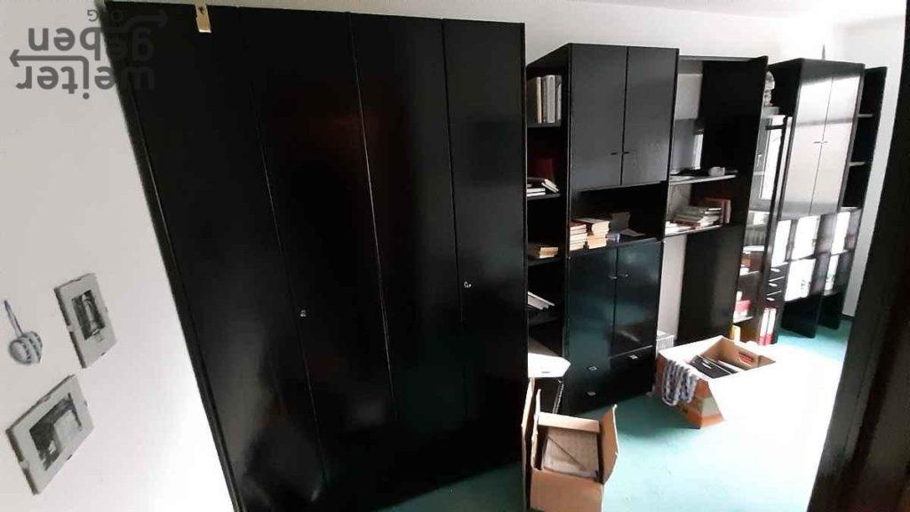 zu sehen: schwarze Wohnzimmerwand mit vielen offenen Fächern