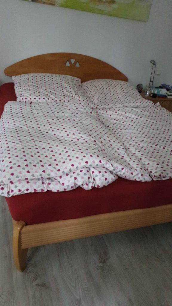 man sieht: großes Doppelbett aus angenehm braunem Buchenholz, darauf liegt eine rote Matratze und ein mit Herzen bedruckt, darunter sieht eine rote Matratze und eine mit verschiedenfarbigen Herzen bedruckte weise Bettwäsche