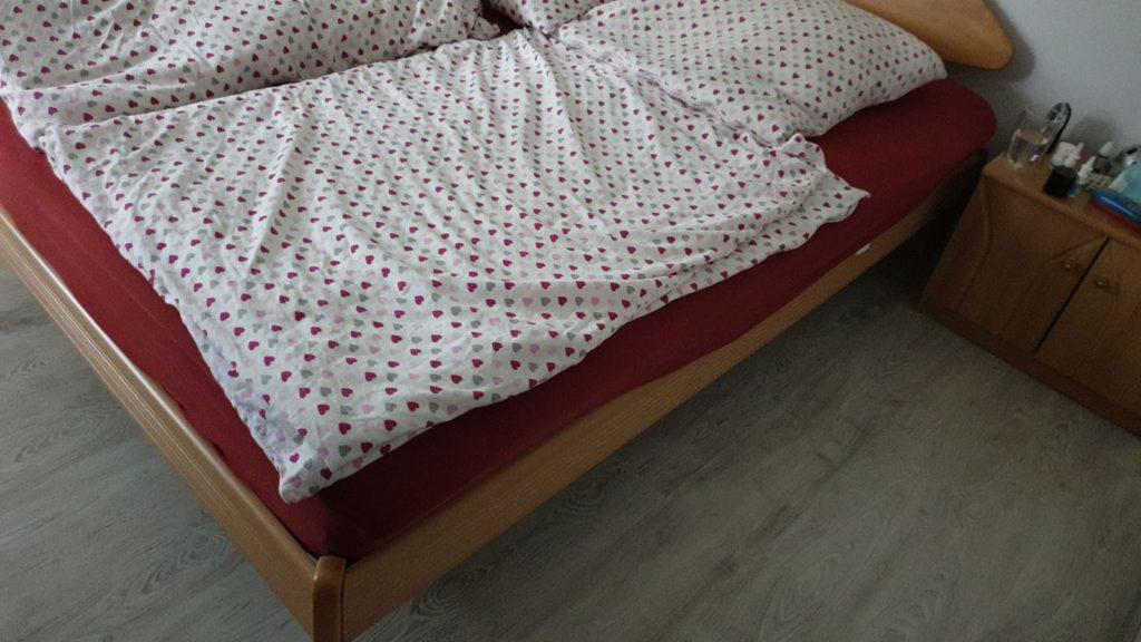 man sieht: weise Bettdecke mit verschieden farbigen Herzen bedruckt, darunter sieht eine rote Matratze und eine Bettleiste aus Buchenholz