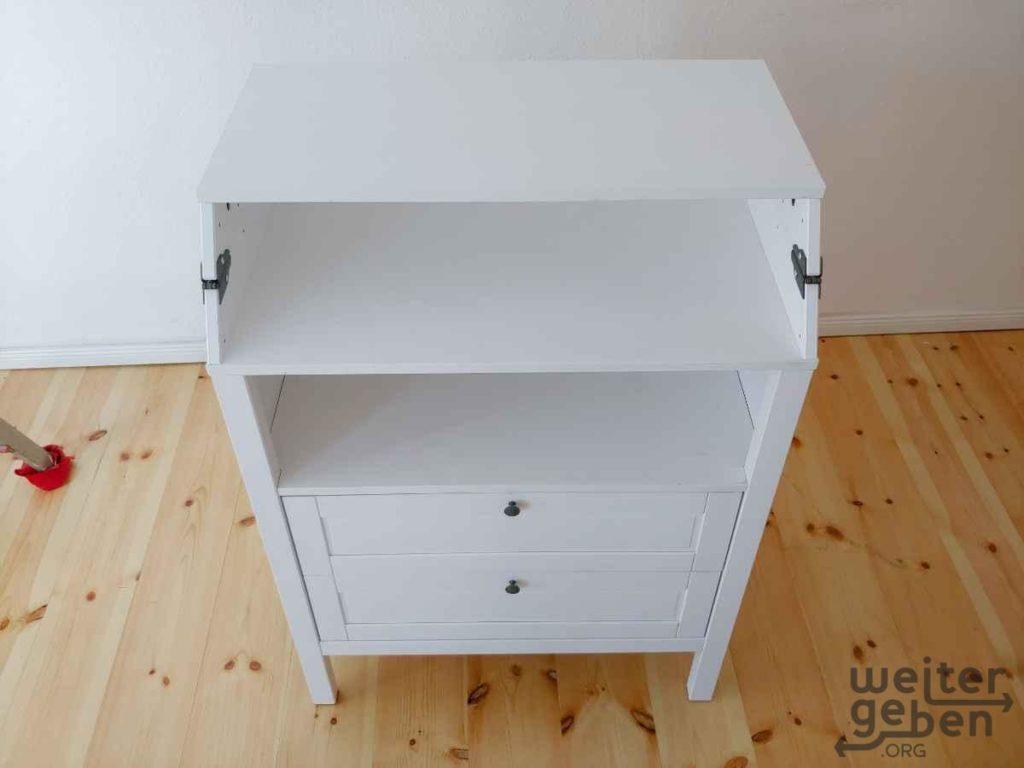 Zu sehen: hüfthohe Kommode. Unten 2 Schubladen und darüber 2 offenen Fächern eines davon umklappbar als Wickelauflage