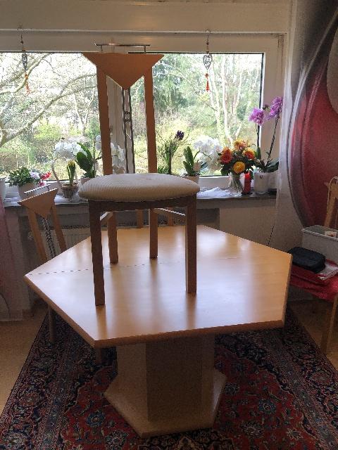 zu sehen: ein 6-Eckiger Holztisch. Darauf ein moderner gepolsterter Holzstuhl mit schmaler Rückenlehne, welche aus 4 Elementen besteht