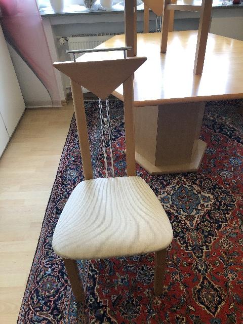 zu sehen: moderner gepolsterter Holzstuhl mit schmaler Rückenlehne, welche aus zwei Holz- und zwei Metall-ementen besteht