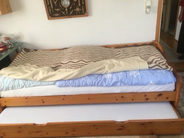 zu sehen: ein Einzellbett mit massivem, dezenten Holzrahmen, welches man zu zwei Betten ausziehen kann