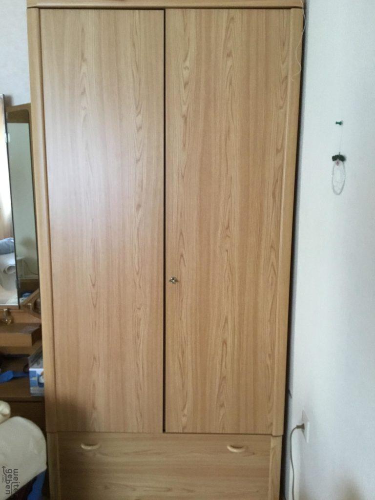 zu sehen: heller, schmaler Kleiderschrank, unten mit einer Schublade