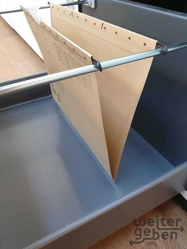 zu sehen: ein herausgezogender Schub eines Aktenschranks in dem eine einzige Hängemappe hängt,