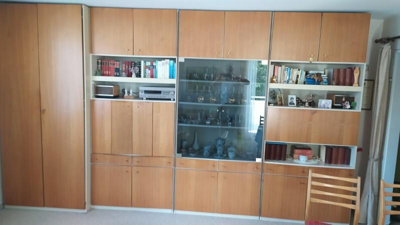 zu sehen: Wohnzimmerschrankwand mit drei offenen Bereichen für z.B. Bücher und ganz in der mitte gut 1x1 Meter ein Glasfenster und dahiner vier bereiche für Dekoratives