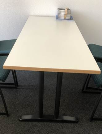 zu sehen: großer, rechteckiger Bürotisch mit heller massiver Holzplatte und links und rechts stabilen Metallfüßen
