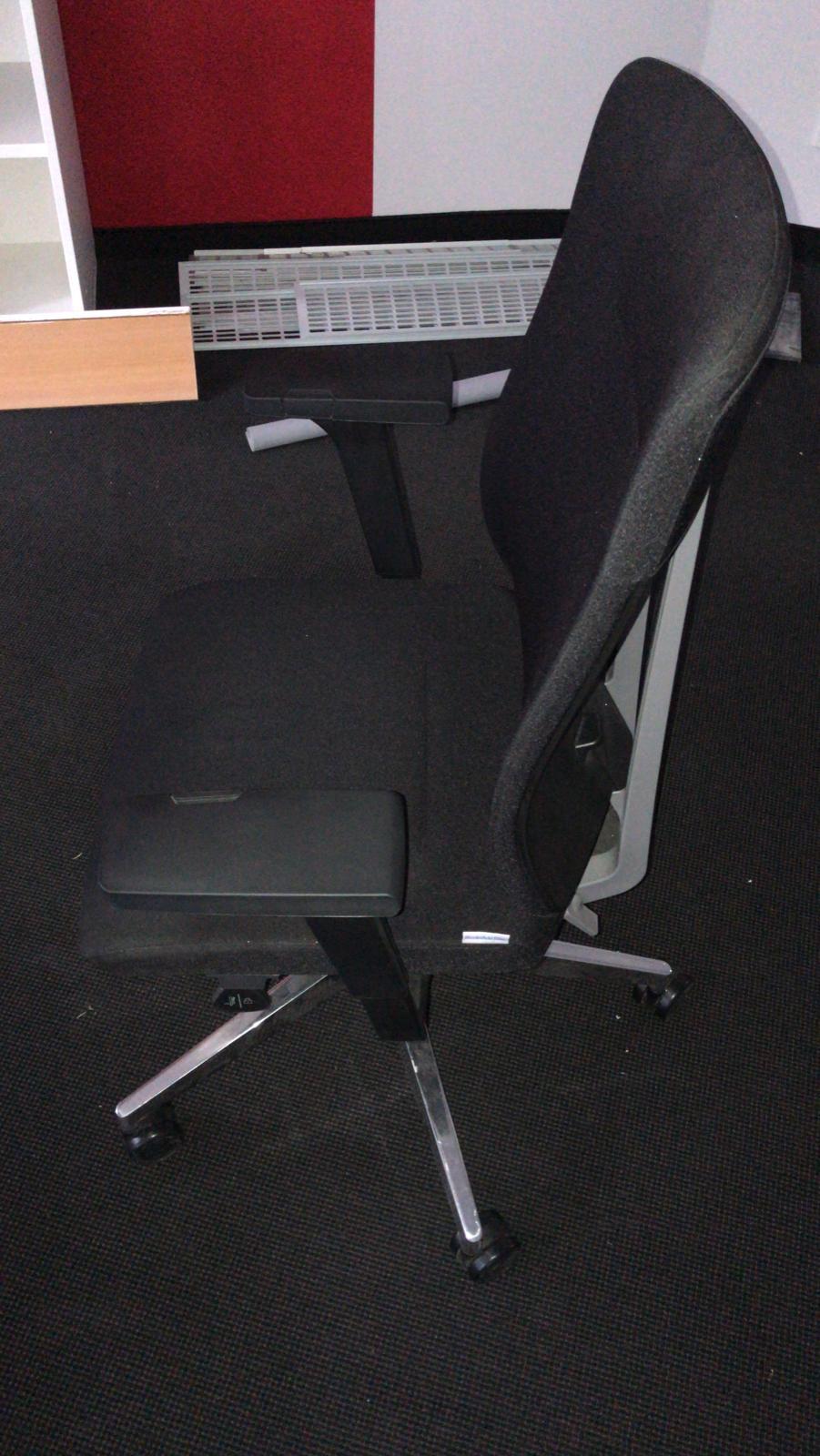 zu sehen: schwarzer Bürostuhl mit hoher Kopflehne und links und rechts Armlehnen