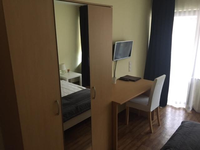 zu sehen: dreitüriger Kleiderschrank eine Tür verspiegelt, sowie kleiner Schreibtisch, Fernseher und Stuhl