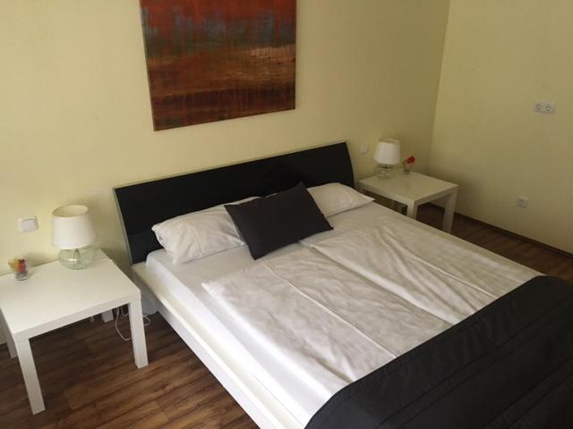 zu sehen: Doppelbett mit links und rechts zwei kleinen weißen Tischchen mit Tischlampen sowie einem großen Bild über dem Bett