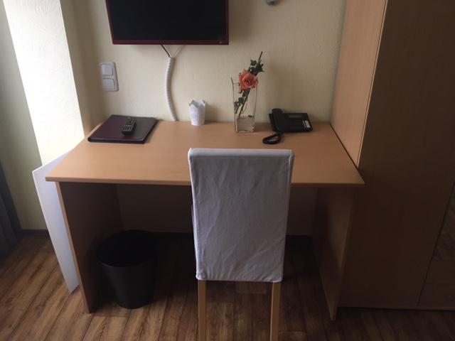 zu sehen: kleiner Schreibtisch, Fernseher, Stuhl und Tischlampe
