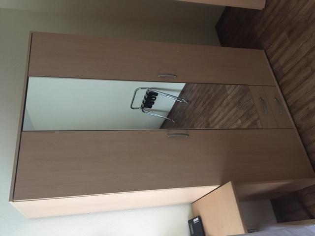 zu sehen: dreitüriger Kleiderschrank eine Tür verspiegelt, sowie kleiner Schreibtisch