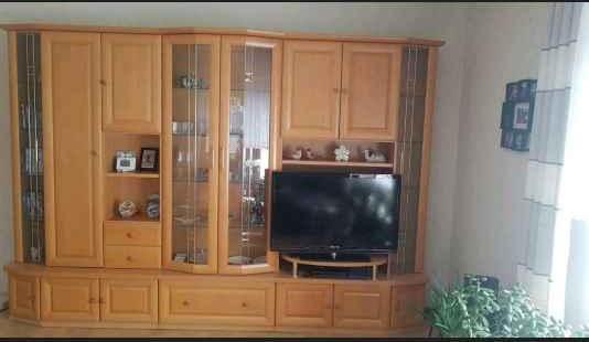 zu sehen: eine 3teilige Wohnwand. Mittleres Teil hat oben eine große schöne Glasvitrine. Alle drei haben unten je einen ca. 30cm hohen Schub/-lade