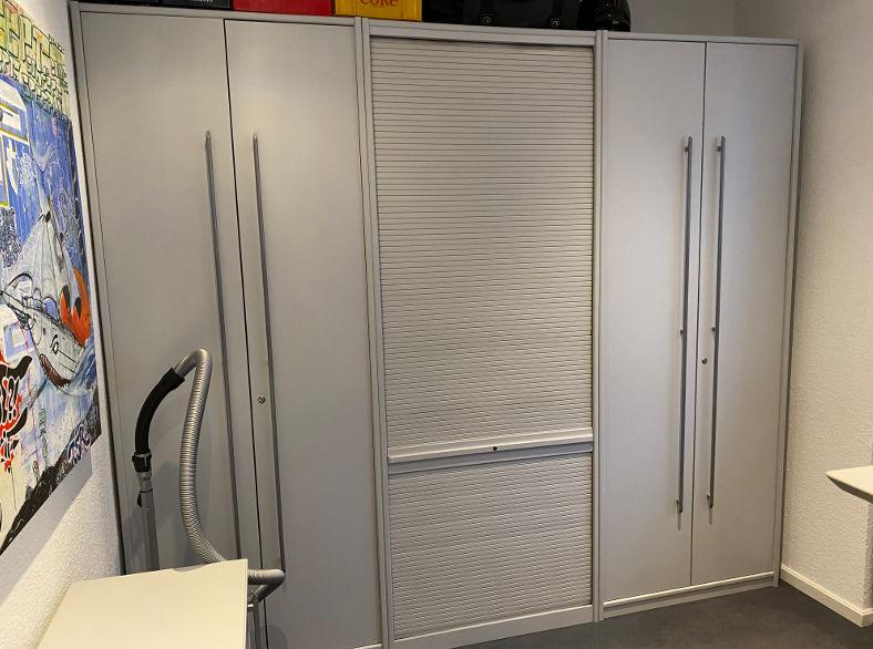 zu sehen: grauer dreiteiliger Büroschrank links und rechts, Doppeltüren der mittlere Schrank hat Rollladen