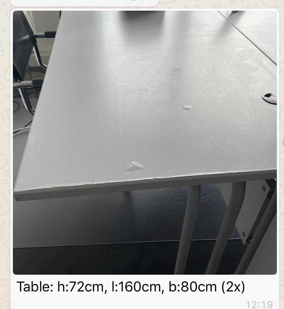 rechteckige Schreibtische mit zwei Öffnungen für Kabel, einer hat Blasen in der Oberseite der Tischplatte