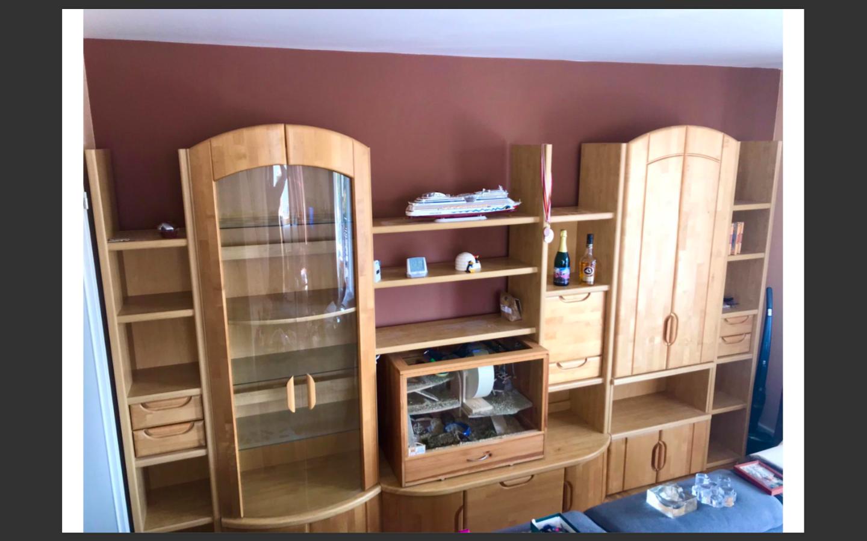 zu sehen: eine moderne Holzschrankwand mit vielen offenen Regalen, oft gebogen, mit einem hohen Regal welches auf fast der vollständigen Höhe zwei Glastür hat.